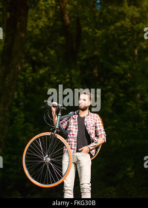The blue -eyed handsome young man dressed casual bike on the shoulder and back green forest - Stock Photo