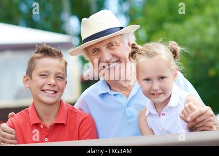 Portrait of happy grandfather with his grandchildren - Stock Photo