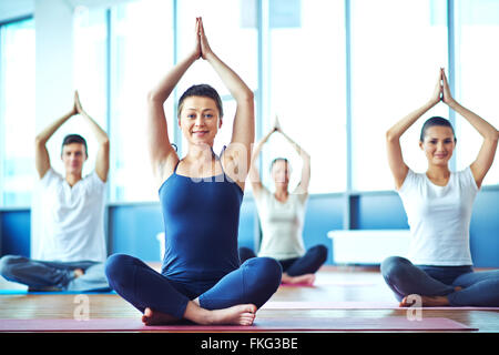 Young woman practicing yoga in yoga class in fitness center - Stock Photo