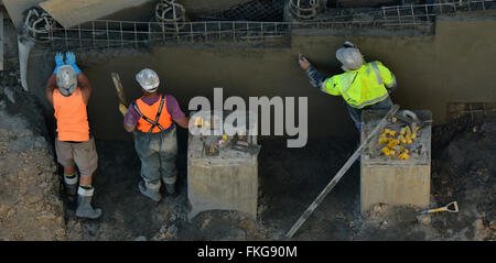 AUCKLAND,  NZL - MAR 09 2016:Concrete plaster men smoothing concrete wall. Plasterwork is one of the most ancient - Stock Photo