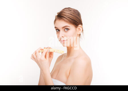 Beauty portrait of pretty young woman filing nails over white background - Stock Photo