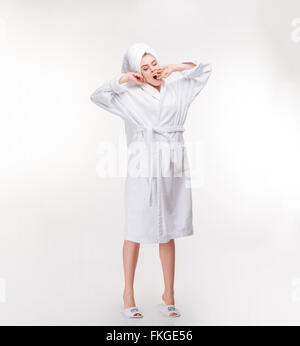 Full length of relaxed sleepy young woman in bathrobe with towel on her head stretching and yawning over white background - Stock Photo