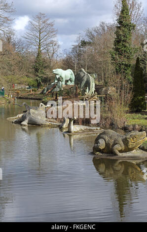 Life-size dinosaur statues in Crystal Palace Park, London. Erected as part of the Great Exhibition in 1854 - Stock Photo