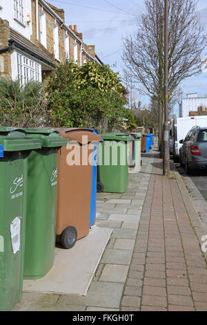 Household refuse recycling bins take up most of the pavement space on a South London street in Southwark - Stock Photo