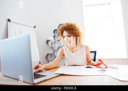 Cheerful curly redhead young woman cutting color paper and using laptop in office - Stock Photo