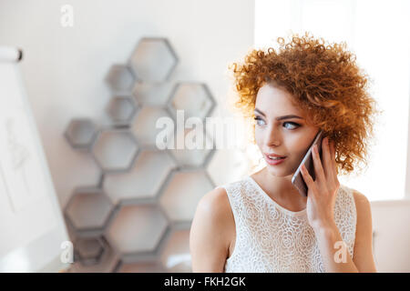 Pensive beautiful young business woman talking on cell phone in office - Stock Photo