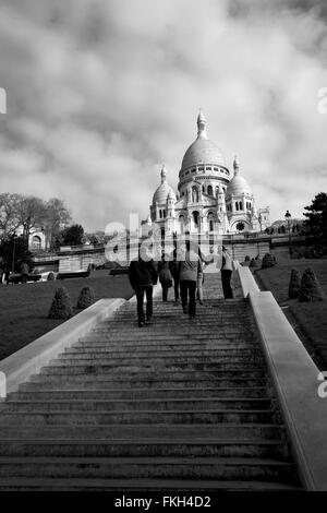 Tourists walking up towards Sacre Coeur (The Basilica of the Sacred Heart of Paris) in Paris, France. - Stock Photo