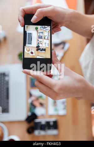 Closeup of hands of young woman taking photos of objects on her workplace using smartphone - Stock Photo