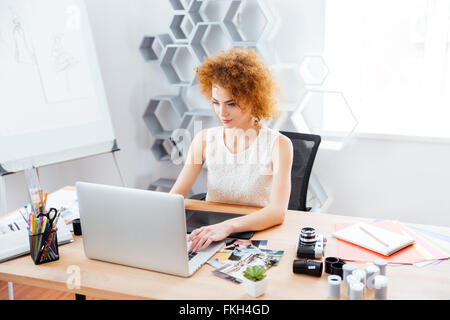 Beautiful curly young woman photographer sitting on workplace and using laptop with graphic tablet - Stock Photo