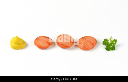 slices of grilled sausage, mustard swirl and fresh parsley on white background - Stock Photo