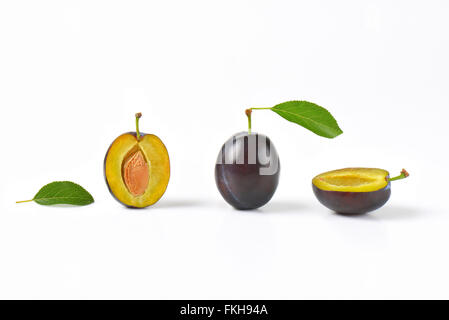 whole and halved plums on white background - Stock Photo