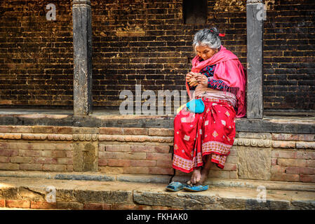 Old woman begs in the street of Bandipur - Stock Photo