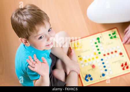 Child playing in board game sitting on floor - Stock Photo