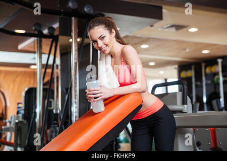 Portrait of happy beautiful young sportswoman with towel and bottle of water on training in gym - Stock Photo