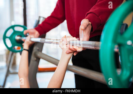 Hands of fitness instructor supporting to young woman athlete working out with barbell in gym - Stock Photo