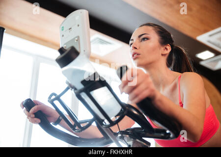 Focused pretty young sportswoman exercising on bicycle in gym - Stock Photo