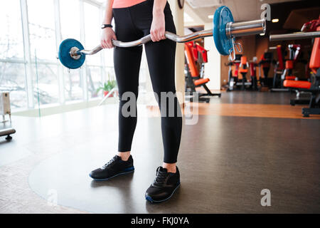 Closeup of legs of young woman athlete standing and exercising with barbell in gym - Stock Photo