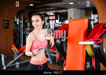 Cheerful beautiful young sportswoman listening to music from mobile phone in gym - Stock Photo