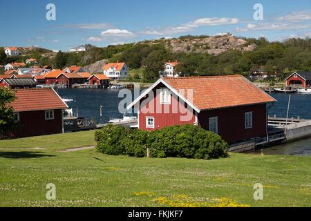 Traditional falu red fishermen's houses and summer houses along coastline, Hamburgsund, Bohuslän Coast, Southwest - Stock Photo