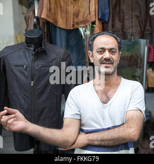 Italian leather vendor standing in front of his stall near the busy central market in Florence, Italy.  Looking - Stock Photo