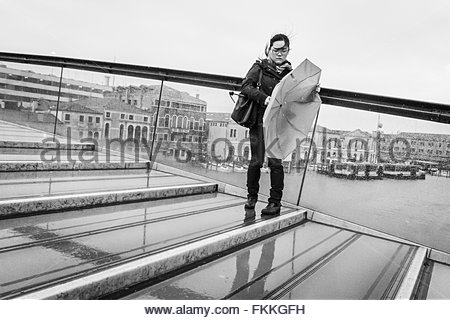 Venice, Italy - 5 March 2016:  MOnochrome image of a young Asian woman fighting with her umbrella on a wet and windy - Stock Photo