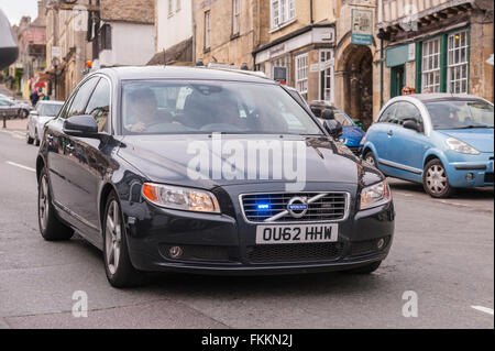 An unmarked police car flashes its blue lights as it speeds through Burford , Oxfordshire , England , Britain , - Stock Photo