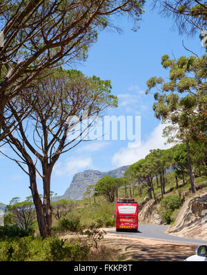 Open top red tourist bus driving up table mountain, Cape Town, South Africa - Stock Photo