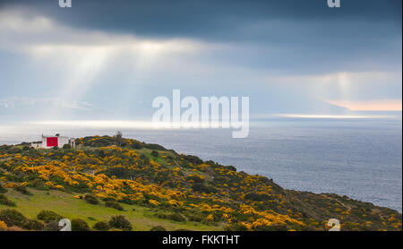 Atlantic Ocean. Summer coastal landscape of Gibraltar strait, Morocco. Small living house with national flag stands - Stock Photo
