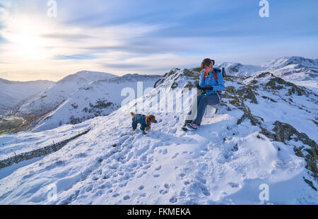 Rest time for a hiker and their dog on Hartsop Above How that leads to Hart Crag in the English Lake District.