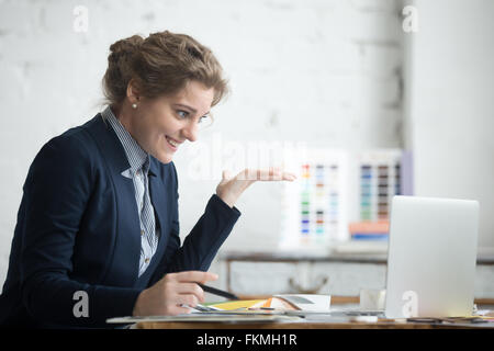 Portrait of young smiling shocked business woman wearing suit sitting at home office desk using laptop, looking - Stock Photo