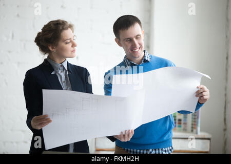 Two colleagues at meeting discussing concept for new project and holding blueprints, planning work. Business discussion - Stock Photo