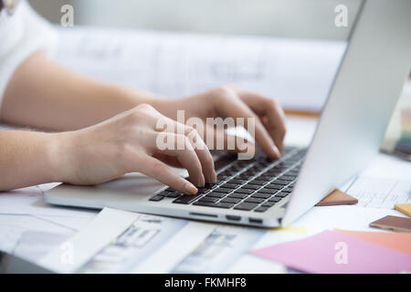 Arms of beautiful young designer woman typing on laptop sitting at home office desk covered in drawings and blueprints - Stock Photo