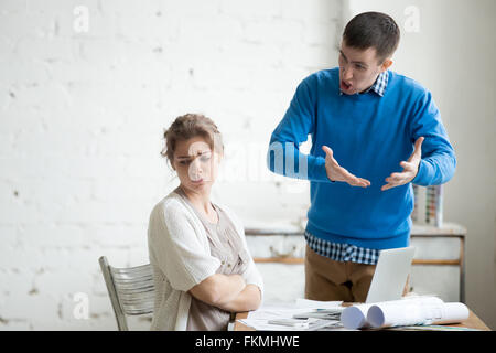 Portrait of two coworkers arguing at work. Staff in the middle of argument at modern office. Young furious man yelling - Stock Photo
