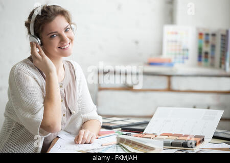 Portrait of beautiful happy smiling young designer woman sitting in headphones at home office desk, working in loft - Stock Photo