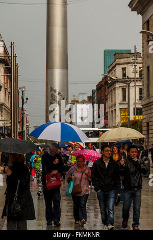 Shoppers on Henry St in Dublin with The Spire of Dublin in the background. - Stock Photo