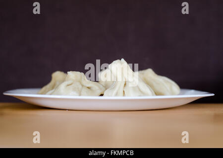 khinkali cooked on a ceramic plate - Stock Photo