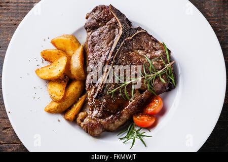 Grilled T-Bone Steak with roasted potato wedges on white plate on wooden background close up - Stock Photo