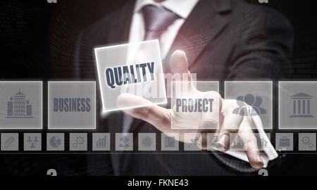 Businessman pressing a Quality concept button. - Stock Photo