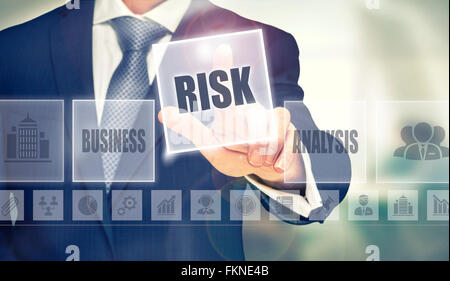 Businessman pressing an Risk concept button. - Stock Photo