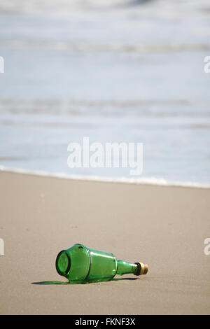 Lost green bottle on the beach - Stock Photo