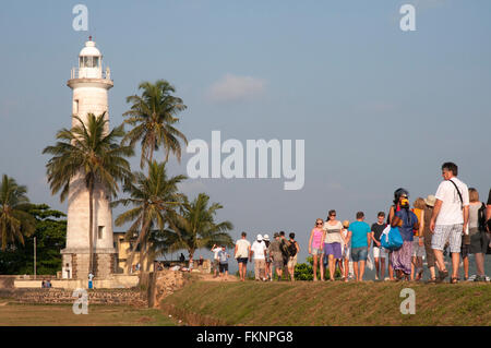 Tourists join local residents in the evening promenade along the ramparts of Galle Fort, Sri Lanka - Stock Photo
