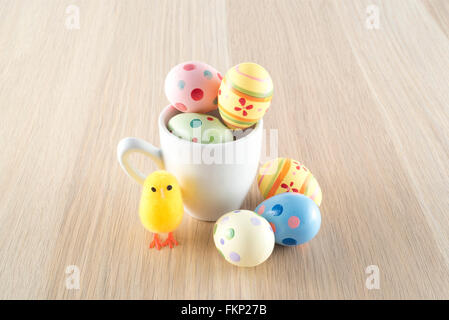 Easter, small chick and colored eggs in a coffee cup - Stock Photo