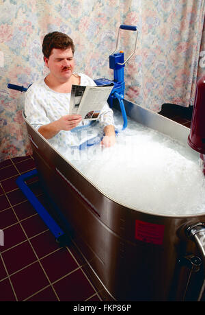 Male patient in whirlpool tub for physical therapy - Stock Photo
