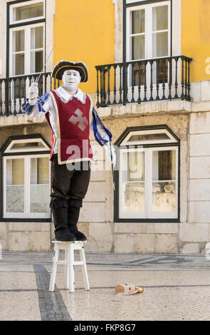 A mime in traditional costume performing on a street in central Lisbon, Portugal - Stock Photo