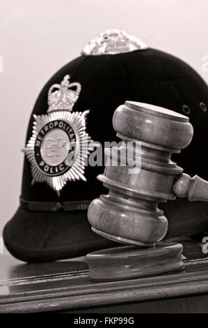Legal concept Metropolitan Police helmet with judges gavel in London law courts situation UK (B&W toned) - Stock Photo