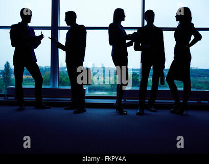 Silhouettes of business team working in office - Stock Photo