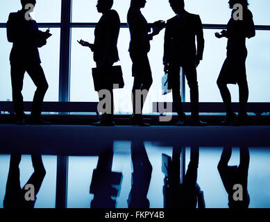 Silhouettes of business people communicating in office - Stock Photo