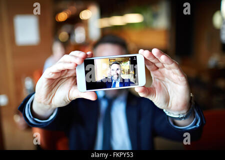 Smiling businessman taking selfie with his cellphone - Stock Photo
