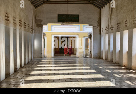 Monks walking in the entrance corridor to Shwezigon Paya, Bagan, Myanmar - Stock Photo