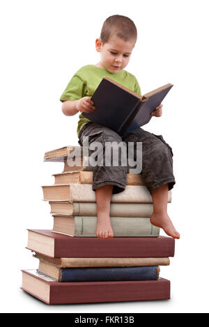 Boy sitting on a big pile of books and reading - Stock Photo